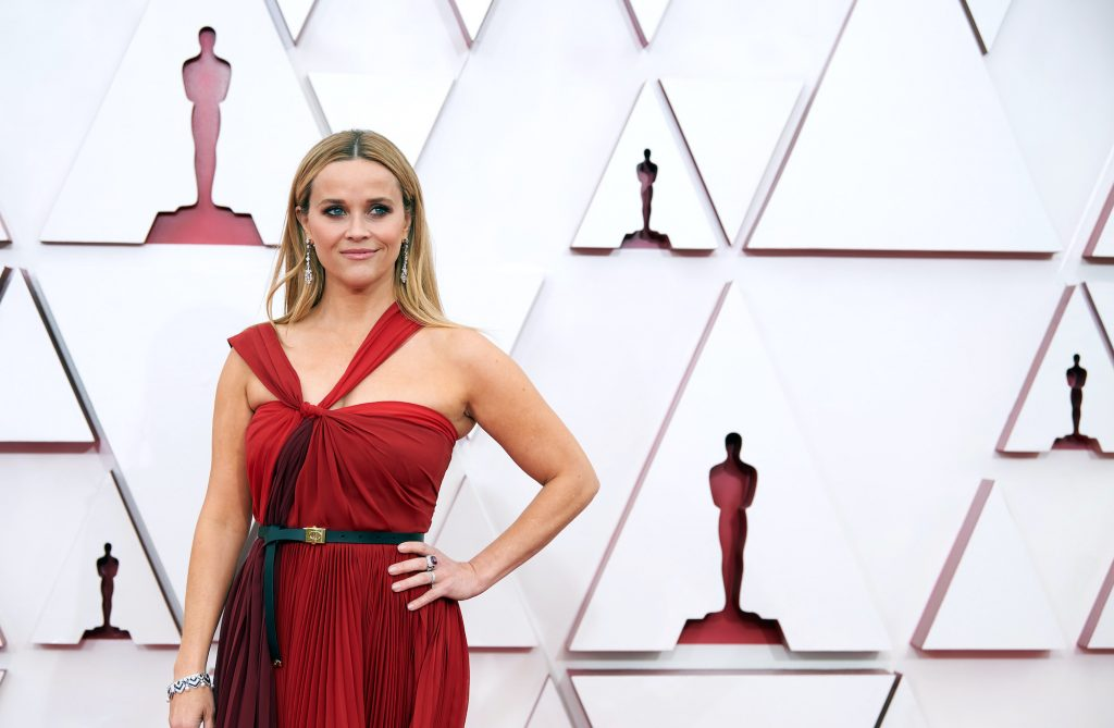 Reese Witherspoon smiling in front of a white background