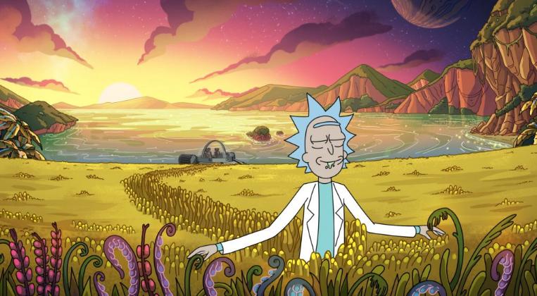 Rick Sanchez of 'Rick and Morty' walks through an idyllic alien field at sunset.