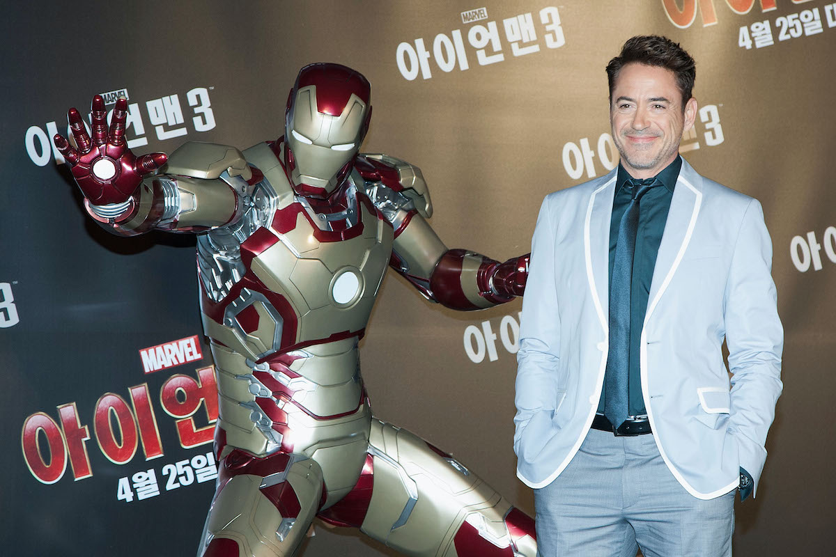 Robert Downey Jr. wears a suit and smiles while posing next to an Iron Man suit