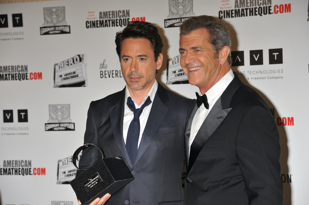 Robert Downey Jr. and Mel Gibson wear suits and pose at at the 25th Annual American Cinematheque Award