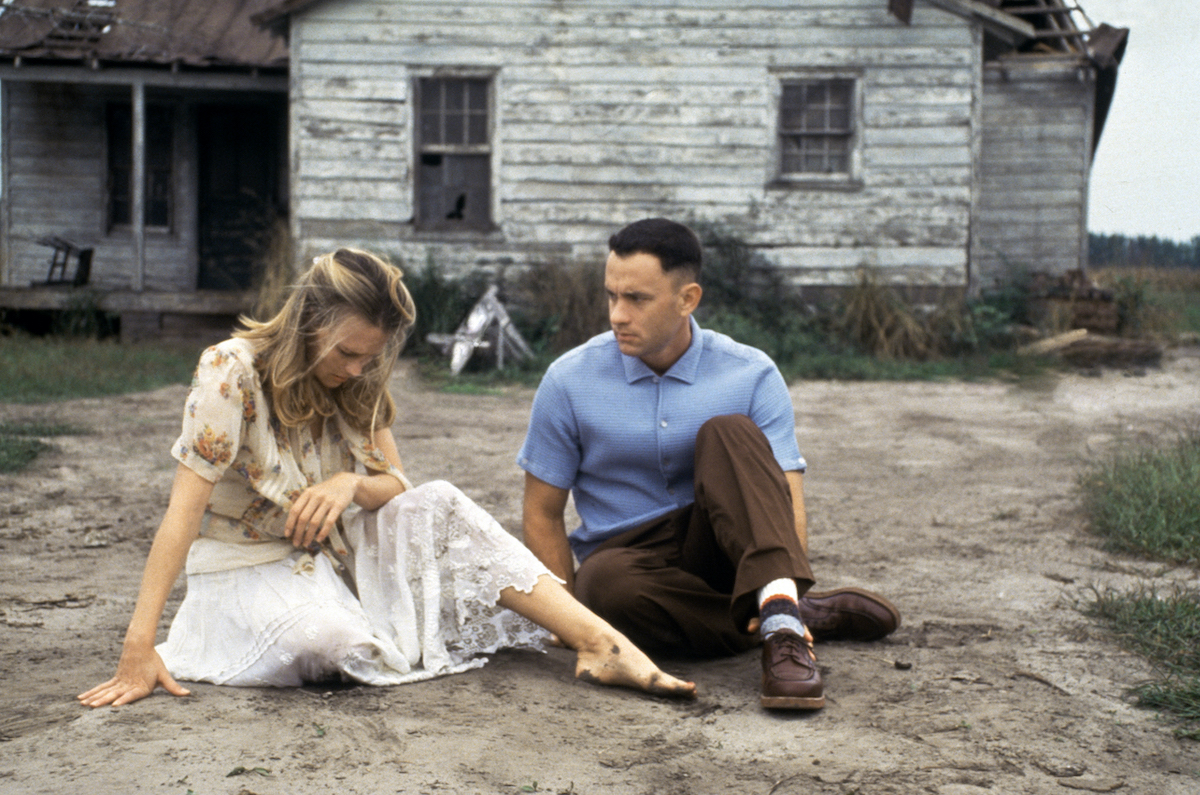 An emotional Jenny (Robin Wright) sits in front of a run-down house while Forrest (Tom Hanks) looks on in the movie 'Forrest Gump'