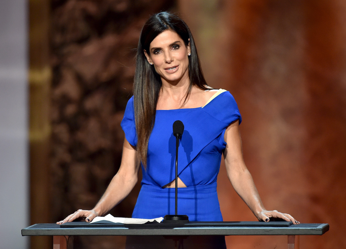 Sandra Bullock wears a blue outfit and speaks onstage at the AFI Life Achievement Award: A Tribute to Jane Fonda