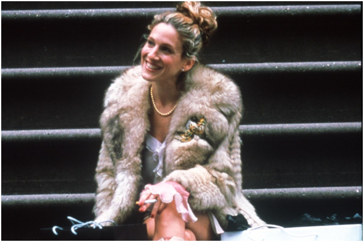 Sarah Jessica Parker smiling on a flight of stairs as Carrie Bradshaw in 'Sex and the City'