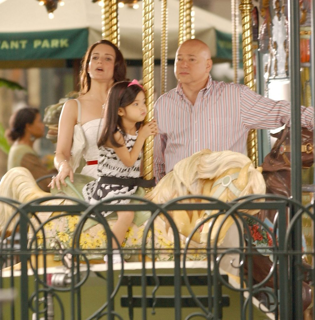 Kristin Davis and Evan Handler stand on the Carousel in Bryant Park with their on-screen daughter
