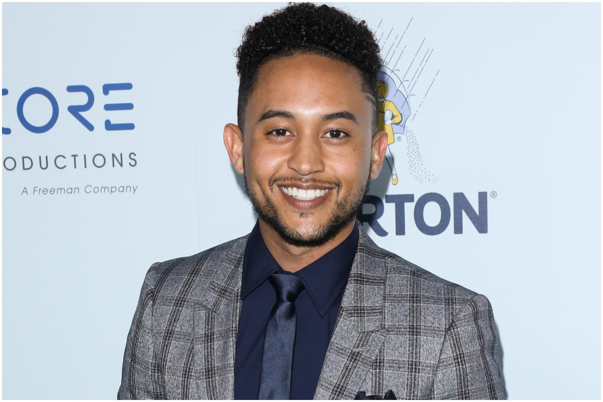 'Smart Guy' actor Tahj Mowry smiling while wearing a suit at a red carpet event.