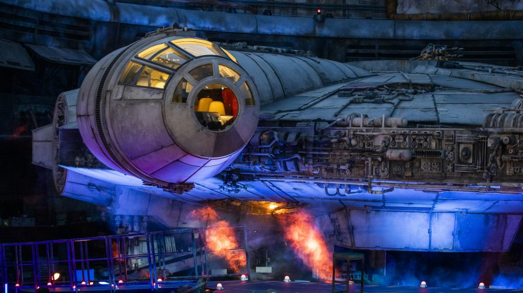 A large crowd gathers in front of the Millennium Falcon at dusk during the Star Wars: Galaxy's Edge unveiling event