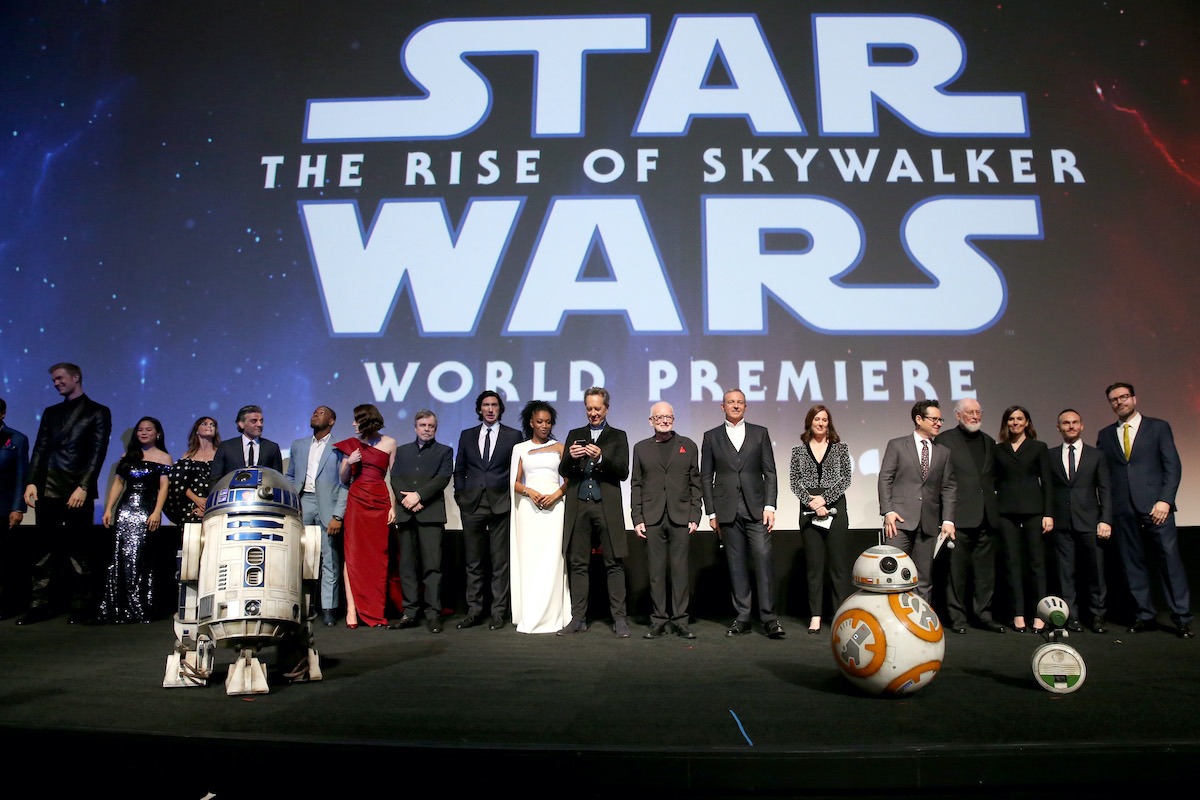 The cast and crew of 'Star Wars: The Rise of Skywalker' pose under a display of the movie's logo