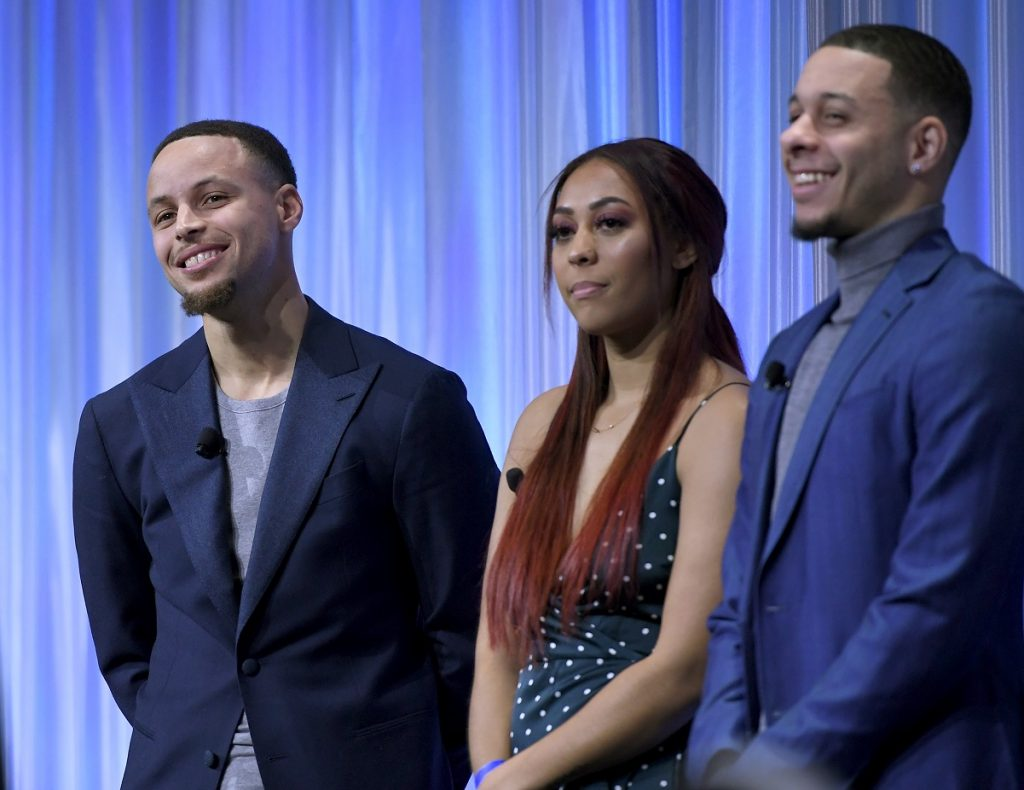 Steph, Sydel, and Seth Curry listen to their father Dell  Curry as he accepts the Home Town Hero Award in Charlotte, North Carolina