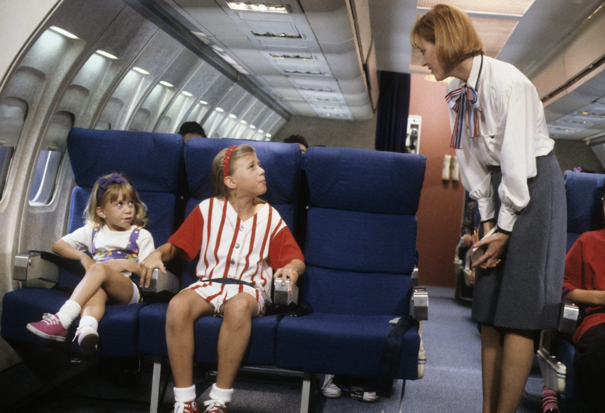 Michelle and Stephanie Tanner on an airplane talking to a flight attendant on an episode of 'Full House'