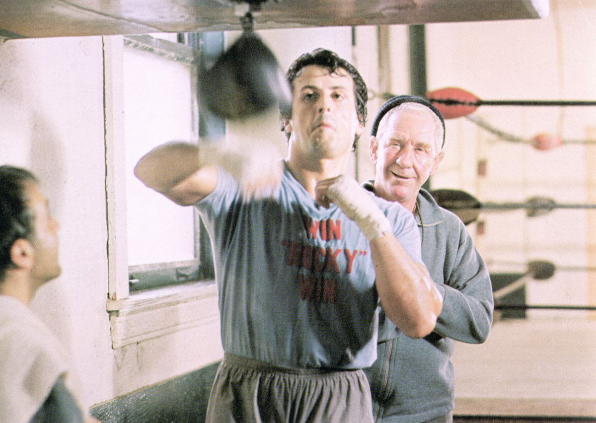 Sylvester Stallone hits a punching bag as Rocky Balboa while Burgess Meredith as Mickey stands behind him in a scene from 'Rocky'