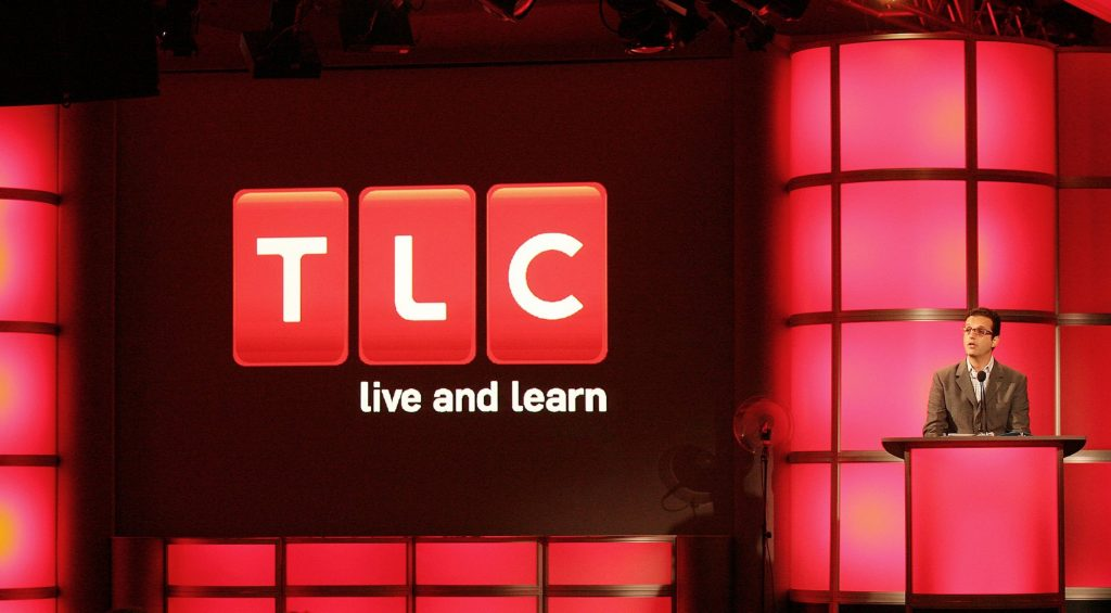 David Abraham speaks at a podium in front of the TLC logo