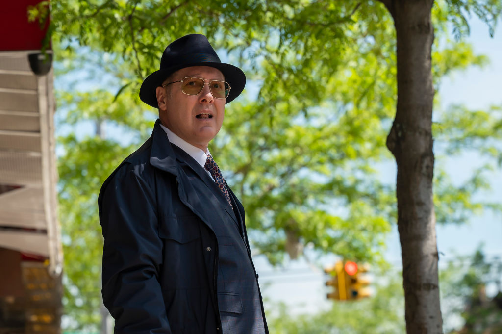 James Spader as Raymond 'Red' Reddington stands outside with a hat and jacket, looking into the distance.