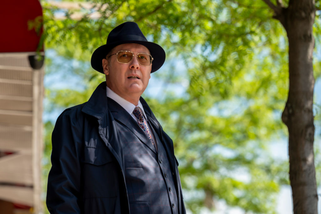 """James Spader as Raymond """"Red"""" Reddington looks into theopen air. He's dressed in a navy trench coat, his trademark hat, and sunglasses."""
