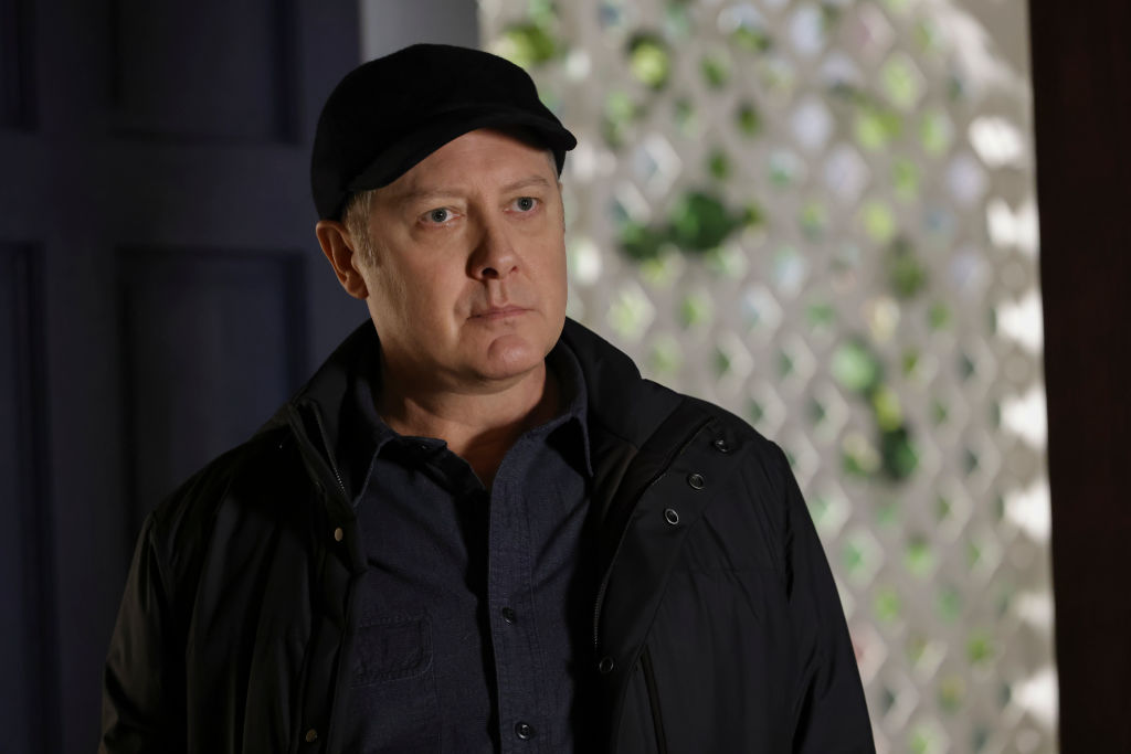 James Spader as Raymond Red' Reddington looks on. He's wearing a dark ball hat and matching jacket.