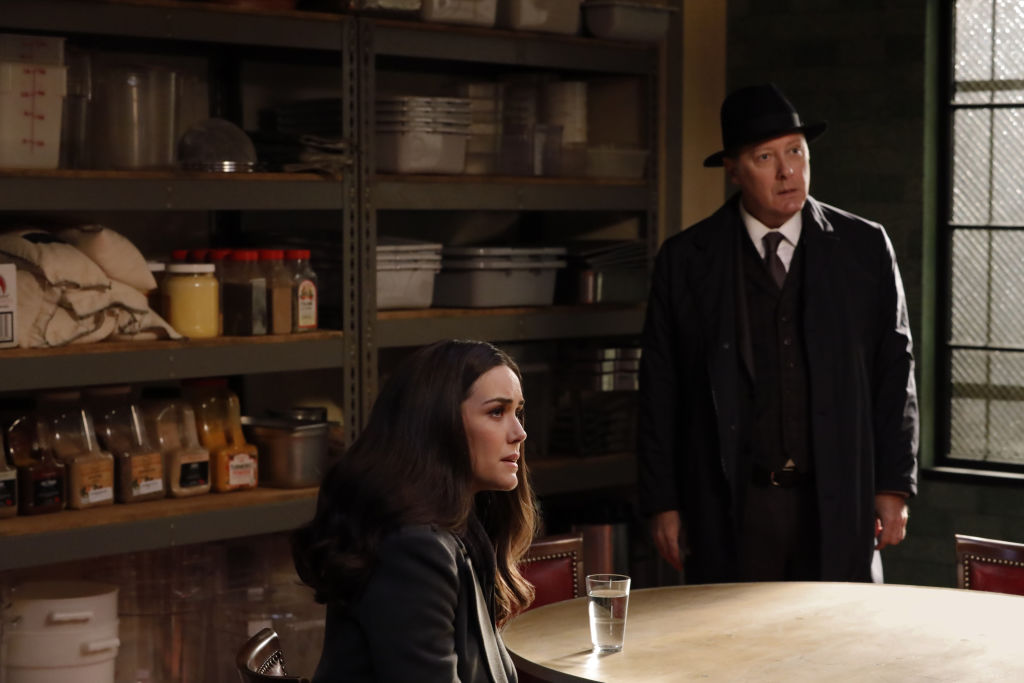 Megan Boone as Liz Keen sits at a table while James Spader as Raymond Reddington stands next to her.