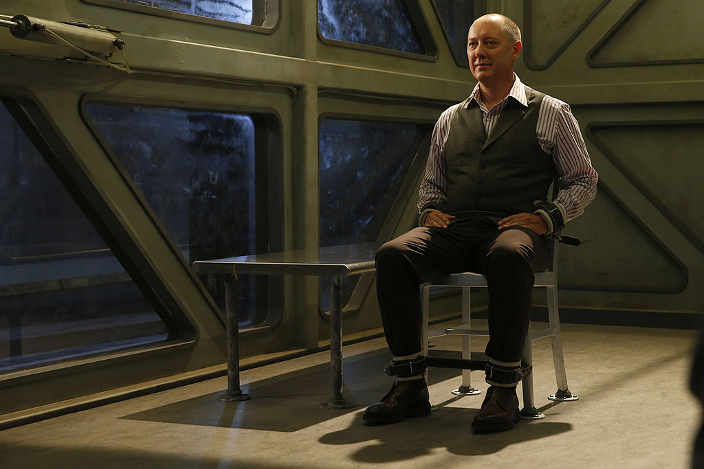 James Spader as Raymond 'Red' Reddington sits smug inside a see-through box which is his temporary jail cell.