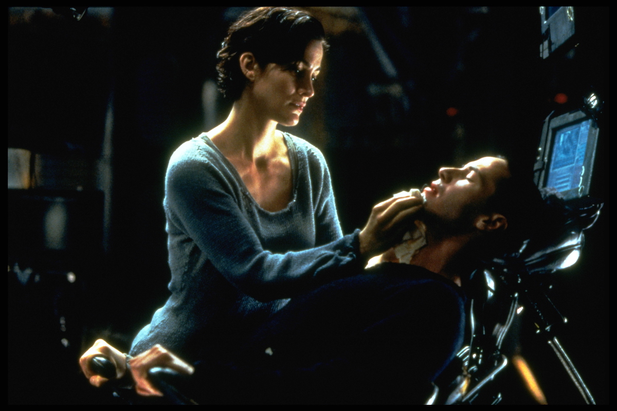 Trinity (Carrie-Anne Moss) stands over Neo (Keanu Reeves) in a scene from 'The Matrix'