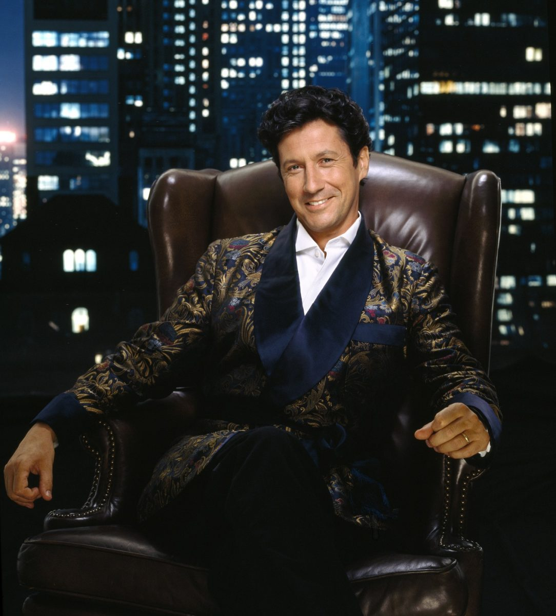 Charles Shaughnessy as Maxwell Sheffield is photographed sitting in a leather chair against a backdrop of the New YorK City skyline
