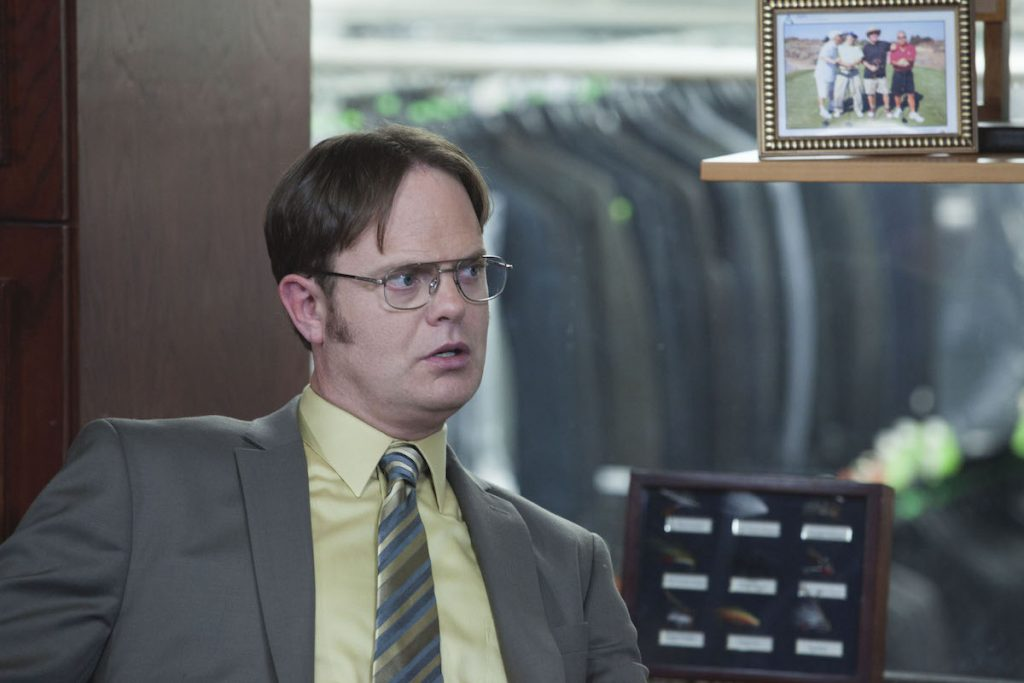 Rainn Wilson as Dwight Schrute sits in a clothing store full of suits on 'The Office'