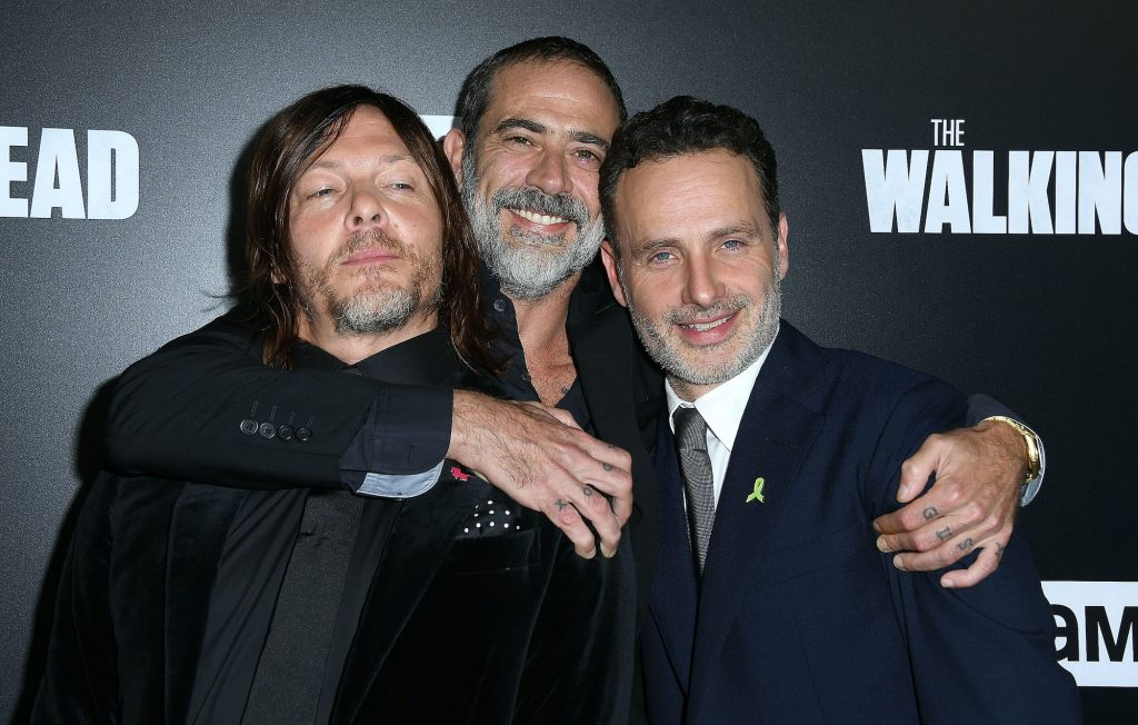 Cast members of 'The Walking Dead' smiling in front of a black background