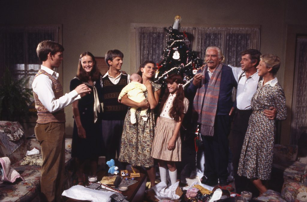 Members of the Walton family standing around a Christmas tree in a 1977 episode of The Waltons