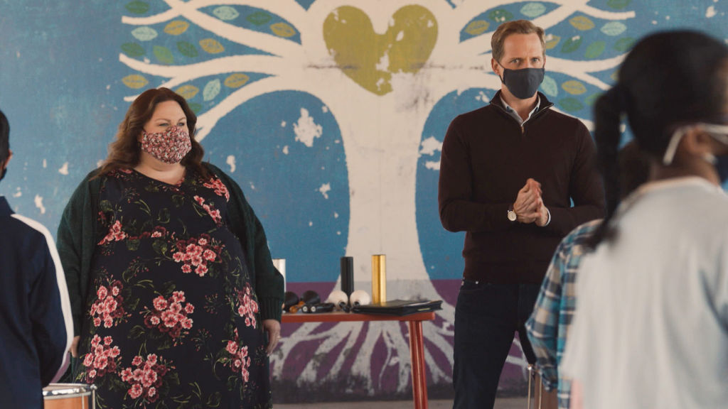 Chrissy Metz as Kate, Chris Geere as Phillip are masked as they stand in front of a crowd.