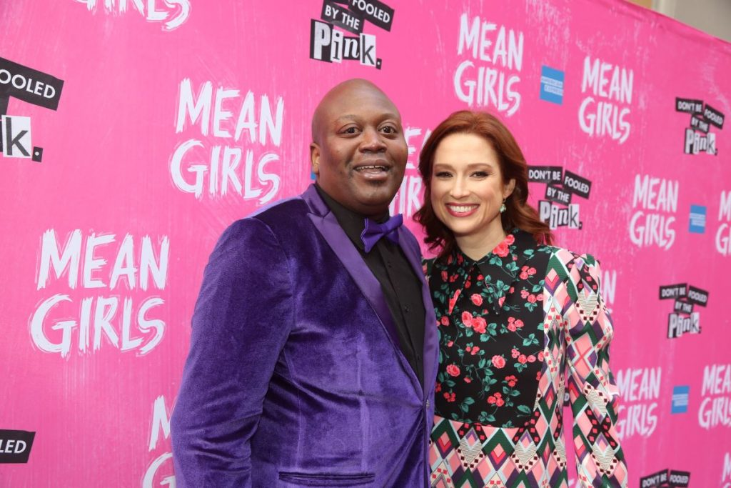 'Unbreakable Kimmie Schmidt' star Tituss Burgess in a purple suit with black shirt and Ellie Kemper in a flower suit