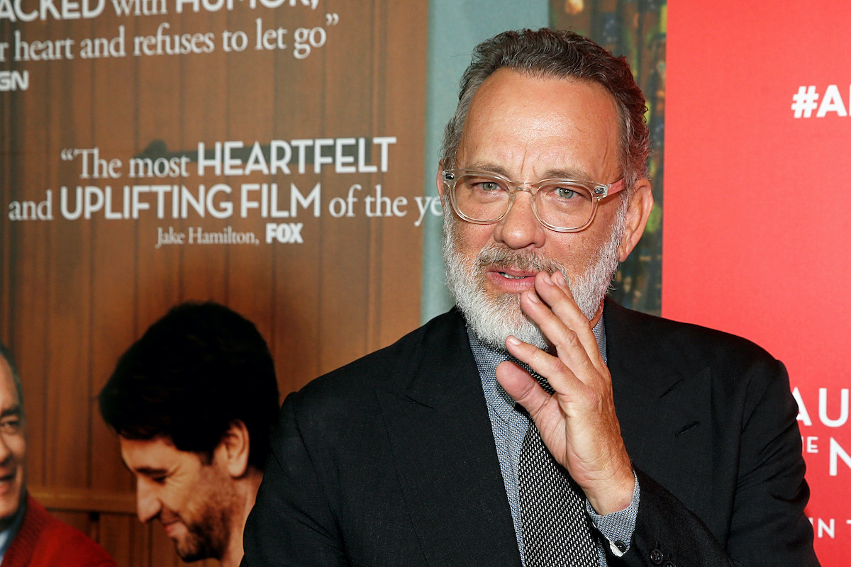 Tom Hanks wears a suit and tie and stands in front of a display for 'A Beautiful Day In The Neighborhood'