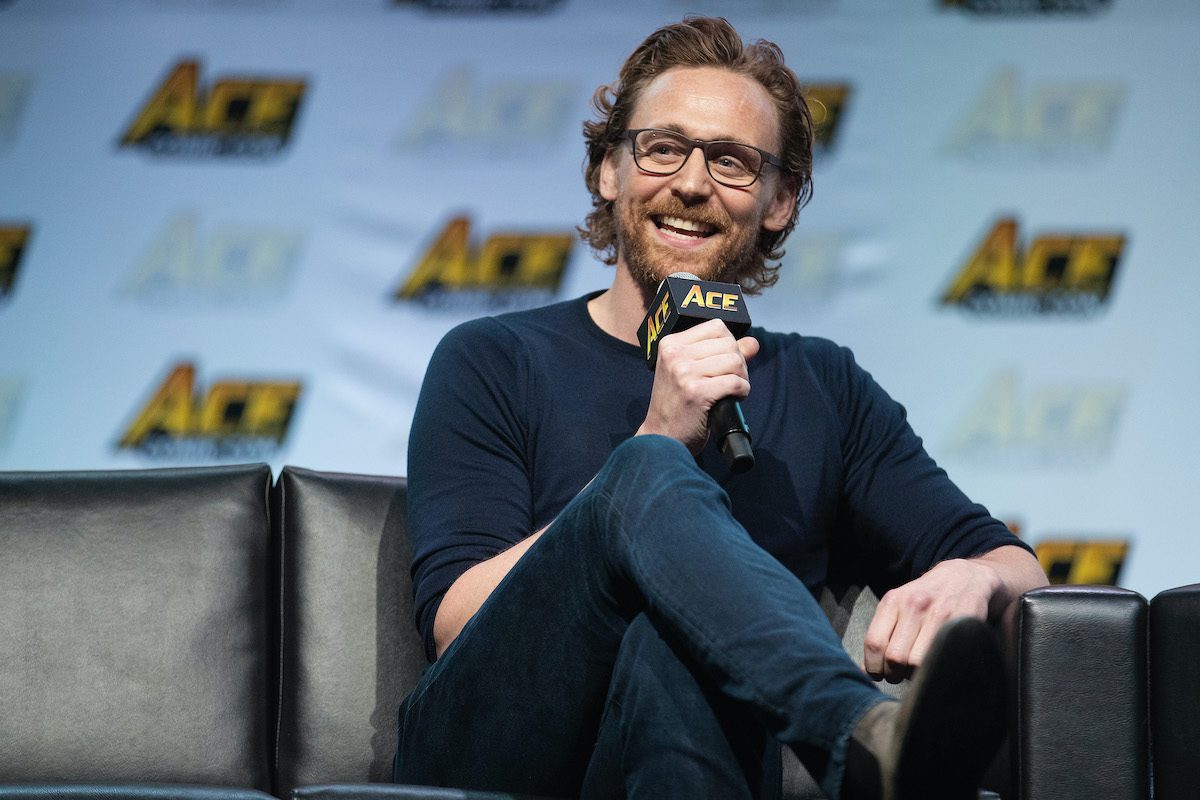 Tom Hiddleston sits on a dark sofa holding a microphone and smiling