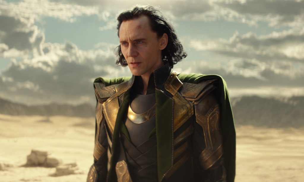 Tom Hiddleston in grey and gold armor with a green cape while standing in a desert as Loki in 'Loki' on Disney+