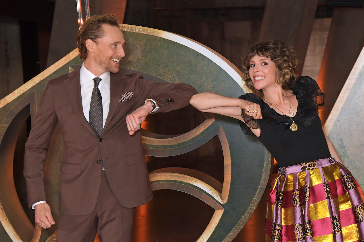 'Loki' stars Tom Hiddleston and Sophia Di Martino bump elbows while standing in front of a display of the show's logo