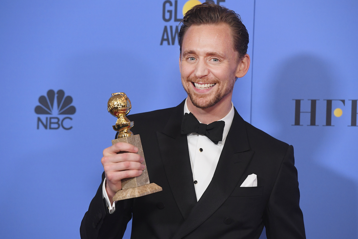 Tom Hiddleston smiles as he poses for cameras holding his Golden Globe for Actor in a Mini-Series or Motion Picture for TV