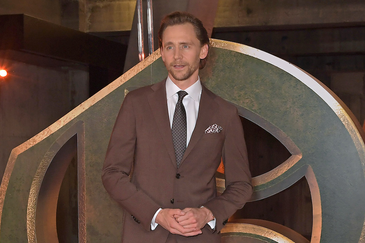 Tom Hiddleston wears a suit and poses in front of a display of the 'Loki' logo
