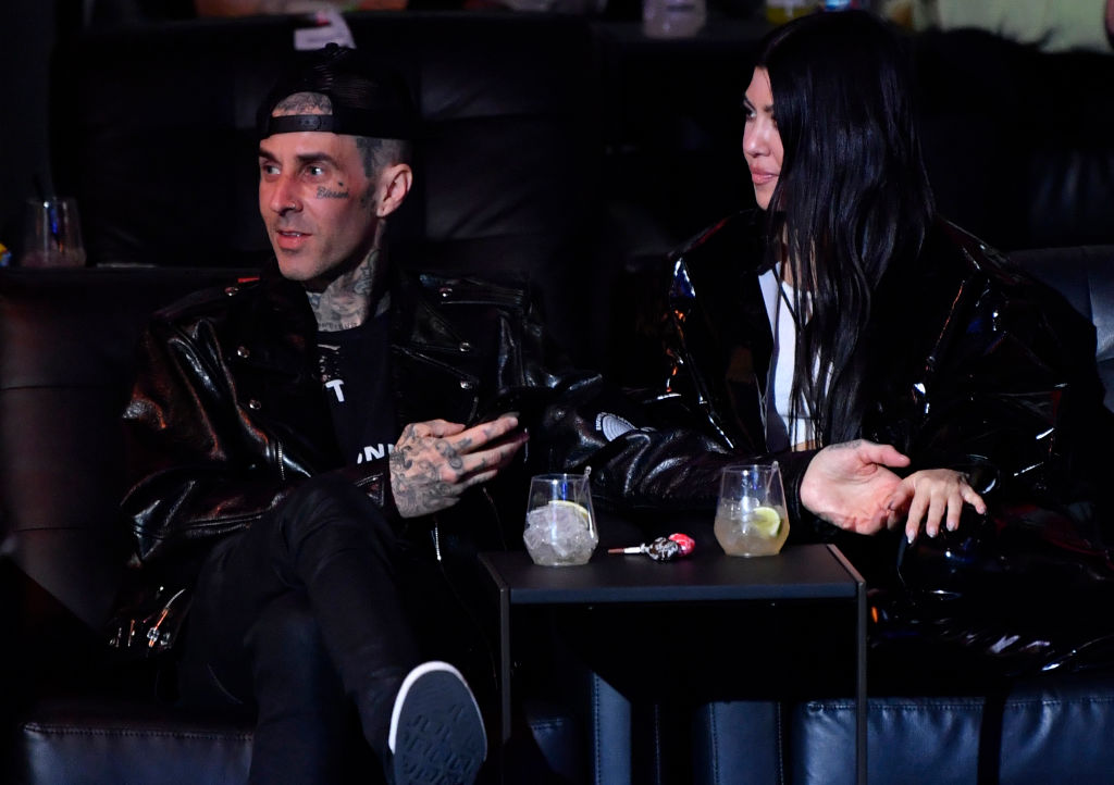 Travis Barker and Kourtney Kardashian sit at a table during the UFC 260 event in Las Vegas.