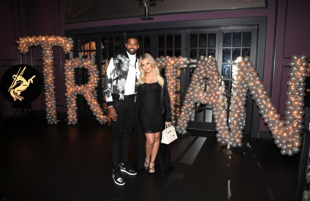 Tristan Thompson in a white shirt and black and white jacket with Khloé Kardashian in a black dress