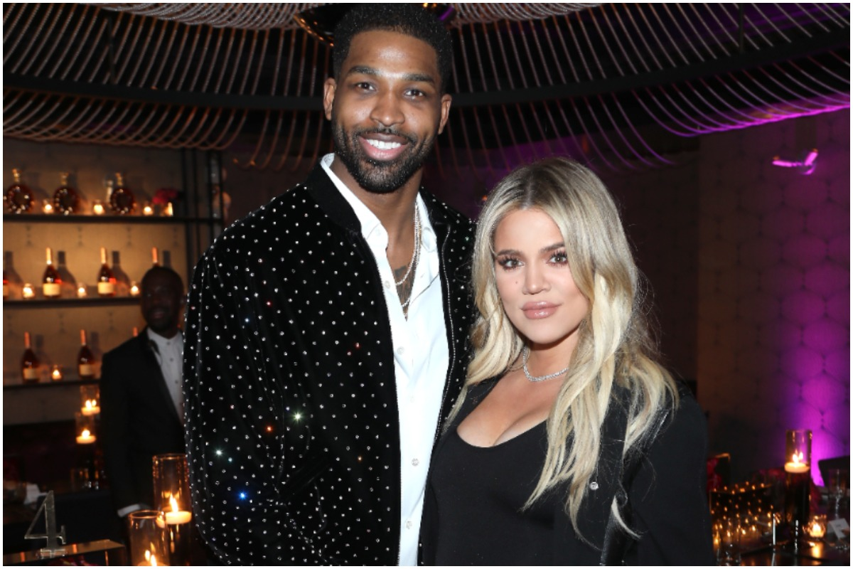 Khloé Kardashian and Tristan Thompson smiling and posing together while wearing black outfits.