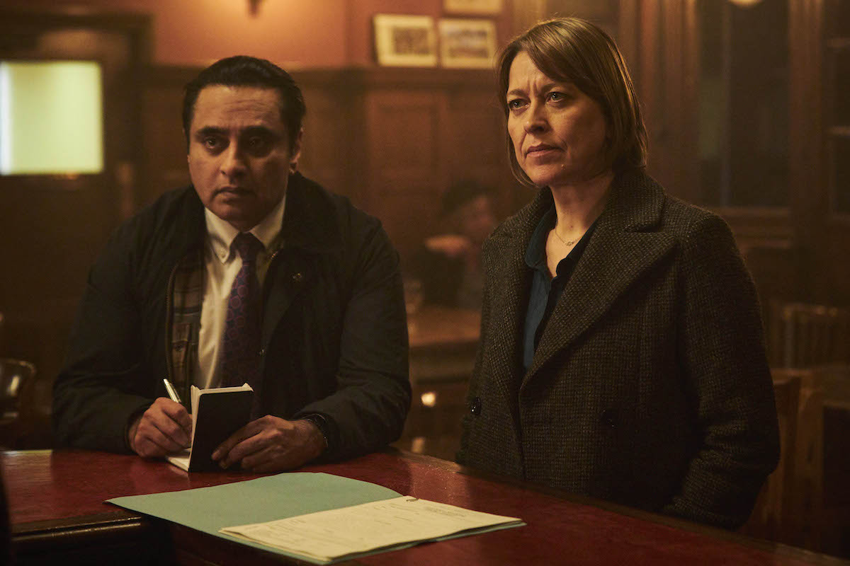 Sunny, taking notes, and Cassie standing at a bar in 'Unforgotten' Season 4