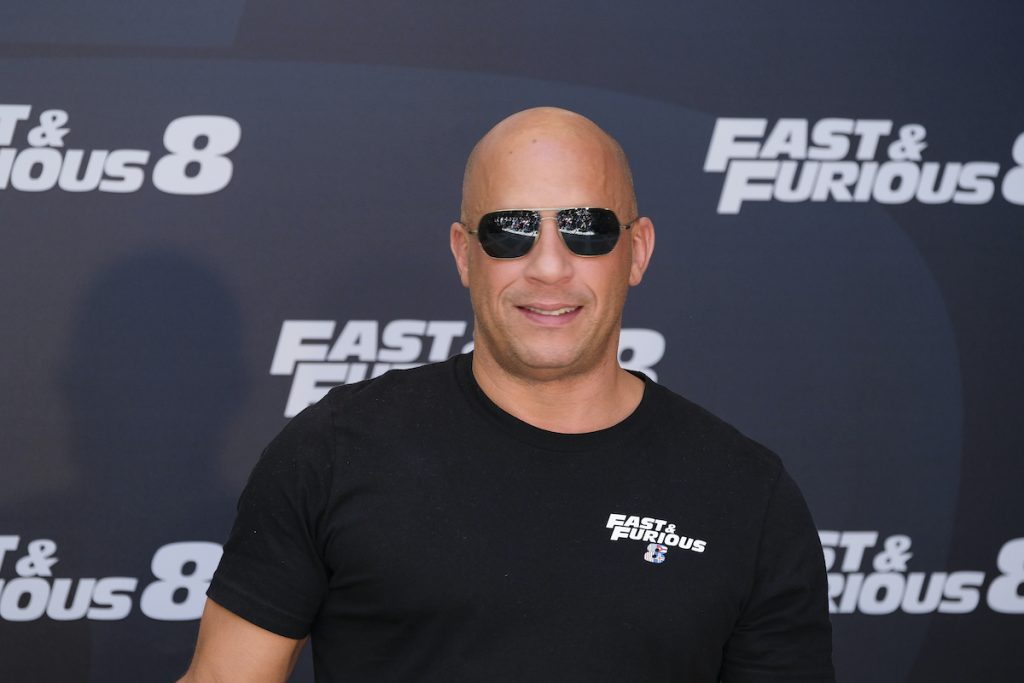 Vin Diesel wears sunglasses and smiles in front of the 'Fast & Furious 8' logo