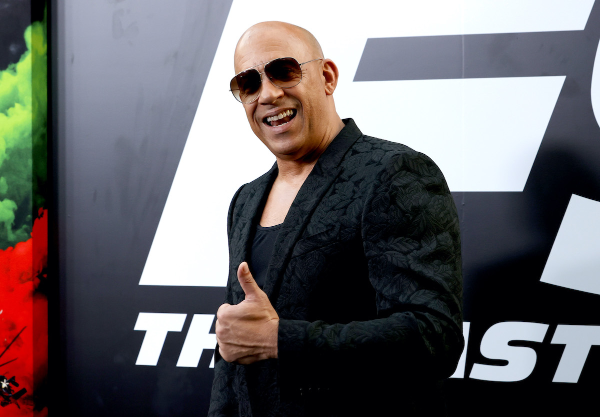 Vin Diesel wears black, smiles, and offers a thumbs up while standing in front of art for 'F9: The Fast Saga'