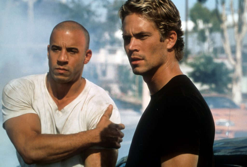 Vin Diesel and Paul Walker stand next to each other in the film 'The Fast And The Furious'