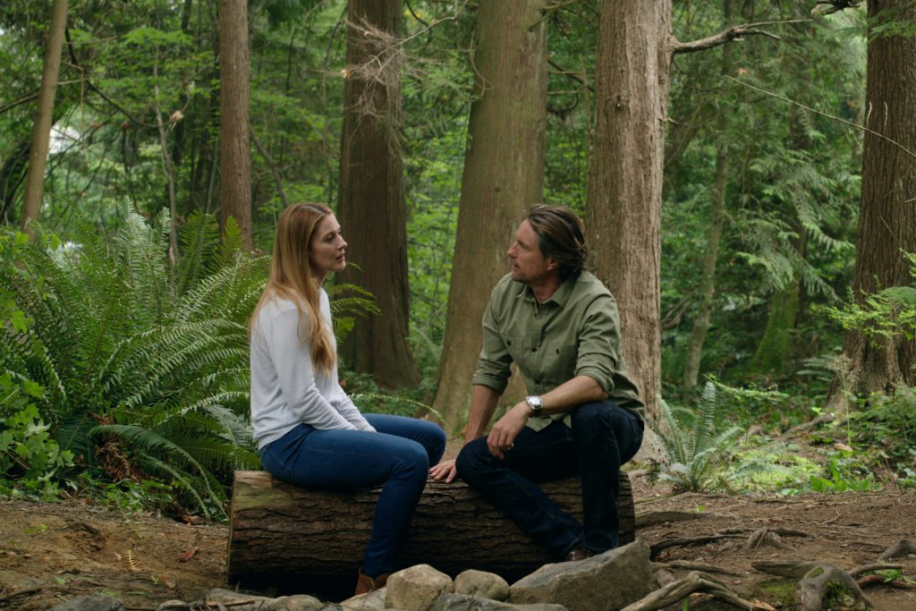 Mel and Jack sitting on a tree trunk in the woods