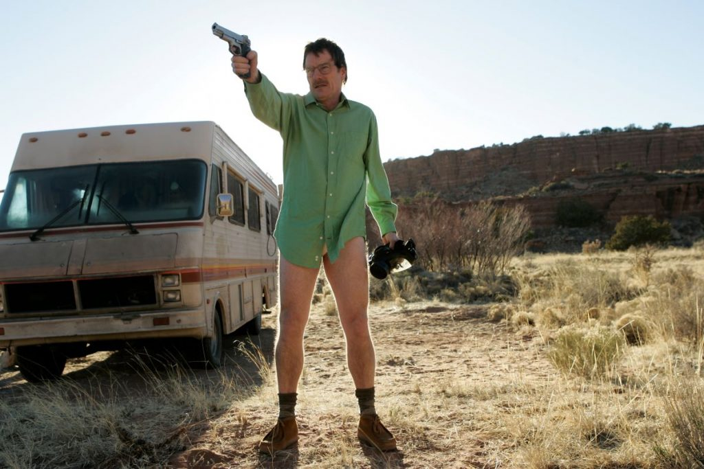 Walter White points a gun as he stands in his underwear, shoes, and a green button-up shirt.