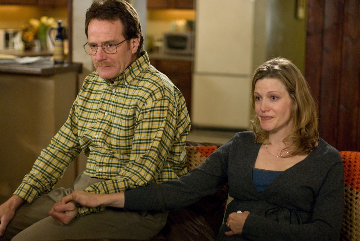 Bryan Cranston as Walter and Anna Gunn as Skyler White hold hands while sitting on a couch together.