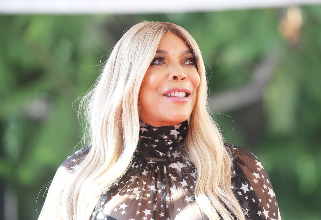 Wendy Williams smiling in front of a blurred background