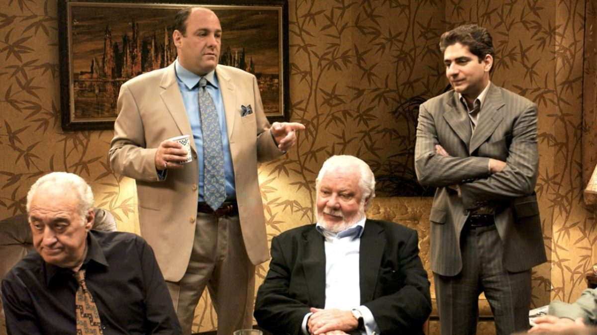 James Gandolfini points as Michael Imperioli looks while others sit around a card table in a 'Sopranos' episode.
