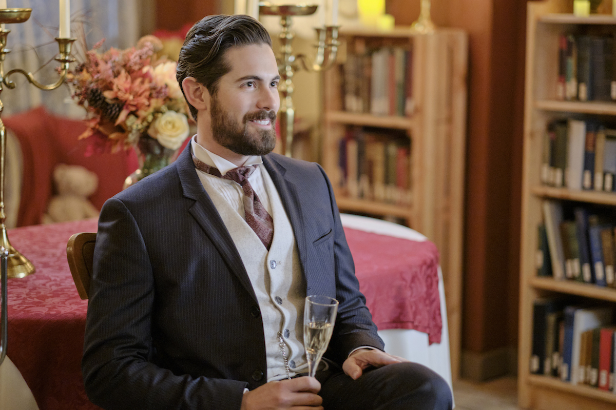 Chris McNally as Lucas, holding as glass of champagne, in 'When Calls the Heart'
