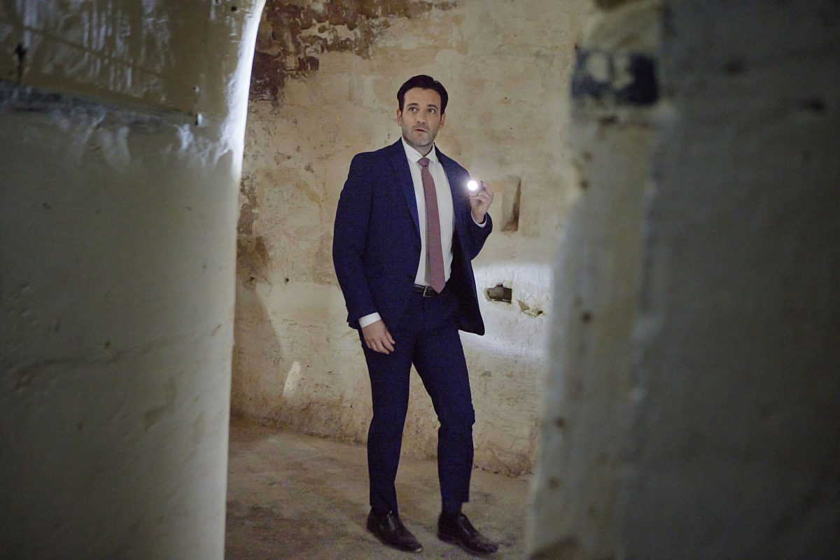 Colin Donnell wearing a suit and holding a flashlight in 'To Catch a Spy'