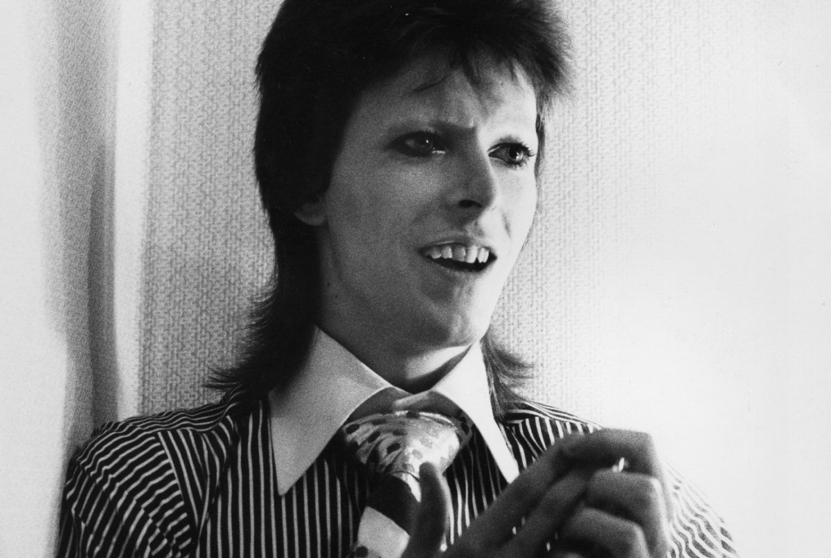 David Bowie smiles an open-mouthed smile while holding his hands together in 1973.
