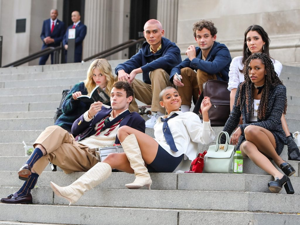 The cast of the 'Gossip Girl' reboot sitting together on stairs outside of a building