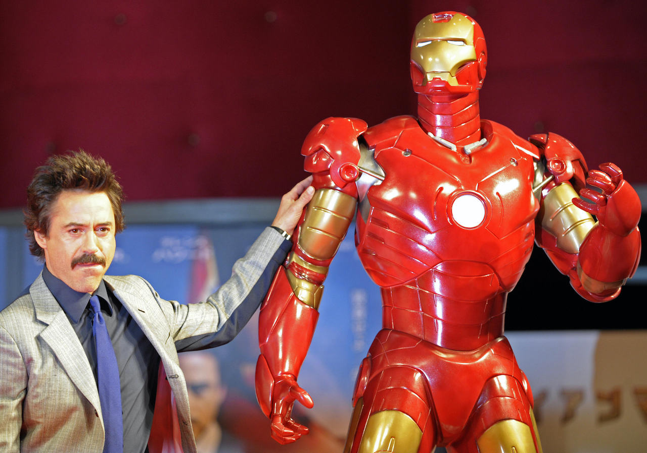 Robert Downey Jr. poses by a life-size Iron Man model during a press conference